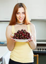 Smiling girl holding plate with cherries at home kitchen Stock Photo