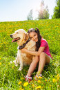Smiling girl hugs cute dog sitting on the grass Royalty Free Stock Photo