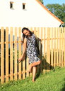 Smiling girl leaning on fence cute young tropical woman in black and white dress wooden by village cottage Stock Photo