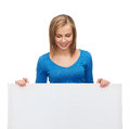Smiling girl lkooking at blank white board advertisement and people concept looking down Stock Photo