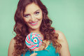 Smiling girl with lollipop candy on teal Royalty Free Stock Photo