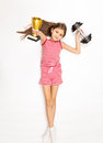 Smiling girl lying on floor with dumbbell and golden trophy cup Royalty Free Stock Photo