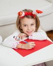 Smiling girl making christmas greeting card portrait of wearing santa headband at home Stock Image