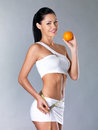 Smiling girl measures figure with an orange Stock Photos