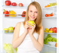 Smiling girl near the refrigerator Lizenzfreies Stockbild