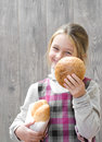 Smiling girl offers bun little tasty Royalty Free Stock Images