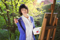Smiling girl painting a canvas outdoor Royalty Free Stock Photo