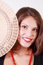 Smiling girl peeks out from behind fan beautiful and looks at camera Royalty Free Stock Images