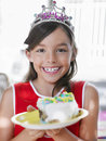 Smiling girl with piece of birthday cake in plate closeup portrait a young Royalty Free Stock Photography