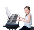 Smiling girl plays on the electric piano cute happy isolated white Royalty Free Stock Images