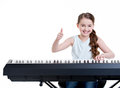 Smiling girl plays on the electric piano cute happy and shows thumbs up isolated white Royalty Free Stock Image