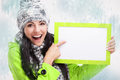 Smiling girl pointing at a blank board and around snowing nice young with with snow background Royalty Free Stock Images
