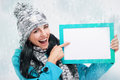 Smiling girl pointing at a blank board and around snowing nice young with with snow background Stock Photos