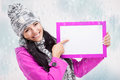 Smiling girl pointing at a blank board and around snowing nice young with with snow background Stock Images
