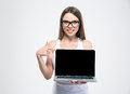 Smiling girl pointing finger on a blank laptop screen Royalty Free Stock Photo