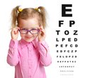 Smiling girl putting on glasses with blurry eye chart behind her isolated white Royalty Free Stock Image