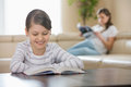 Smiling girl reading book with mother in background at home Royalty Free Stock Photo