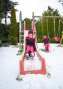 Smiling girl riding down the slide on playground covered with sn cute snow Stock Photo
