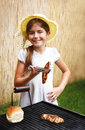 Smiling girl roasting meat on the grill barbecue cooking Stock Photo