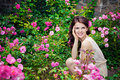 Smiling girl in the rose garden Royalty Free Stock Photo