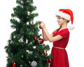 Smiling girl in santa helper hat decorating a tree christmas x mas winter happiness concept Royalty Free Stock Photography