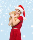 Smiling girl in santa helper hat with teddy bear christmas x mas winter happiness concept Royalty Free Stock Photo