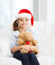 Smiling girl in santa helper hat with teddy bear christmas x mas winter happiness concept at home Stock Photos