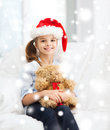 Smiling girl in santa helper hat with teddy bear christmas x mas winter happiness concept at home Royalty Free Stock Image