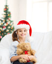 Smiling girl in santa helper hat with teddy bear christmas x mas winter happiness concept at home Stock Images