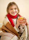 Smiling girl in scarf covered in plaid holding cup of hot tea portrait Stock Image