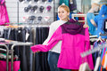Smiling girl selecting a warm jacket in the sport boutique Royalty Free Stock Photo