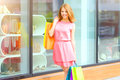 Smiling girl with shopping bags background windows Stock Photos