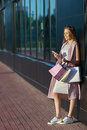 Smiling girl with shopping bags with phone in hand. Shopper. Sales. Concept of woman shopping Royalty Free Stock Photo