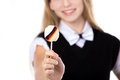 Smiling girl showing candy with germany flag happy cute beautiful blond wearing black formal outfit bowtie lollipop studio shot Stock Photos