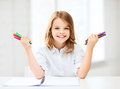 Smiling girl showing colorful felt-tip pens Royalty Free Stock Photo