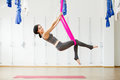 Smiling girl in silk hammock building strength and flexibility of her body