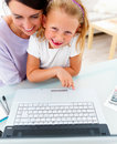 Smiling girl sitting with her mother, using laptop Royalty Free Stock Photos