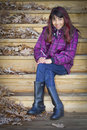 Smiling girl sitting on stairs hispanic in purple jacket and blue jeans wooden with piles of fallen leaves Stock Images