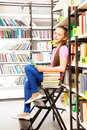 Smiling girl sitting on step ladder in library Royalty Free Stock Photo