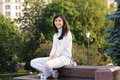 Smiling girl sitting on stone bench Royalty Free Stock Photography