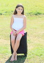 Smiling girl sitting on suitcase barefoot in pink shorts and white t shirt black chech in baggage Royalty Free Stock Images