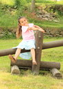 Smiling girl sitting on timber little in blue skirt pink t shirt wooden Royalty Free Stock Photography