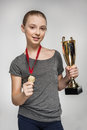 Smiling girl in sportswear holding trophy and medal