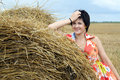 Smiling girl at a stack of straw Royalty Free Stock Images