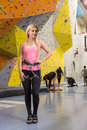 The smiling girl stands with climbing equipment on gym Stock Image