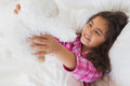 Smiling girl with stuffed toy resting in bed Royalty Free Stock Photo