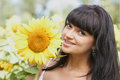 Smiling girl with sunflower outdoors Stock Image