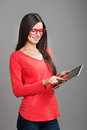 Smiling girl touching pad tablet pc screen in red glasses studio shot on gray background Royalty Free Stock Photos
