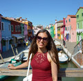 Smiling girl tourist with sunglasses, in a sunny day in Burano island, Venice. Beautiful woman model traveling in Venice, Italy