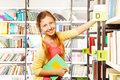 Smiling girl with two braids standing near shelf library and search book one hand and holding a book Royalty Free Stock Photography